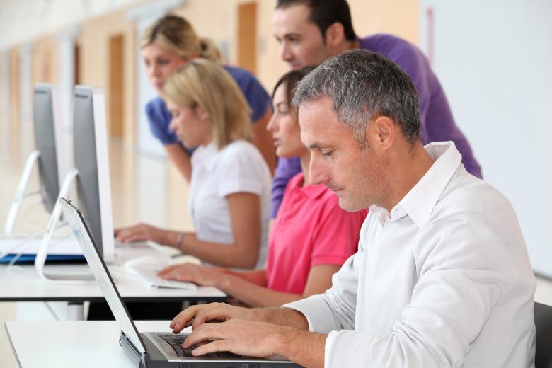 Adult male student works on computer alongside classmates