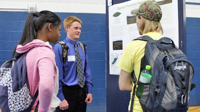 Students discuss poster display at 2016 Academic Festival