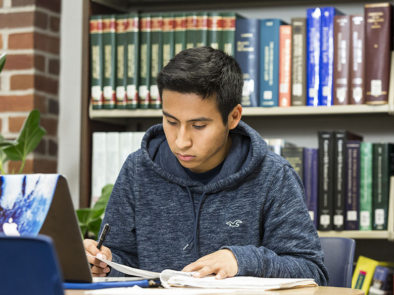 Male student studies in library next to open laptop