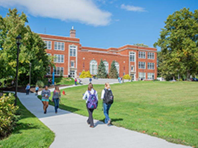 Students walk across campus on a sunny day