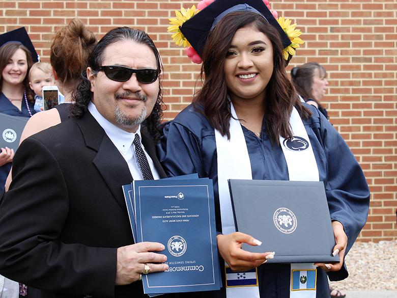 Young female graduate poses with her father at graduation