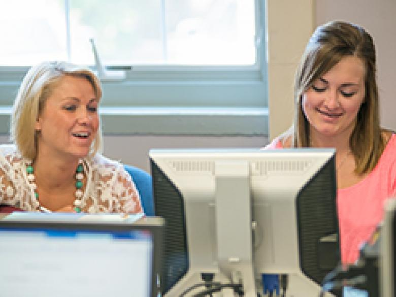 A staff member helps a prospective student apply online
