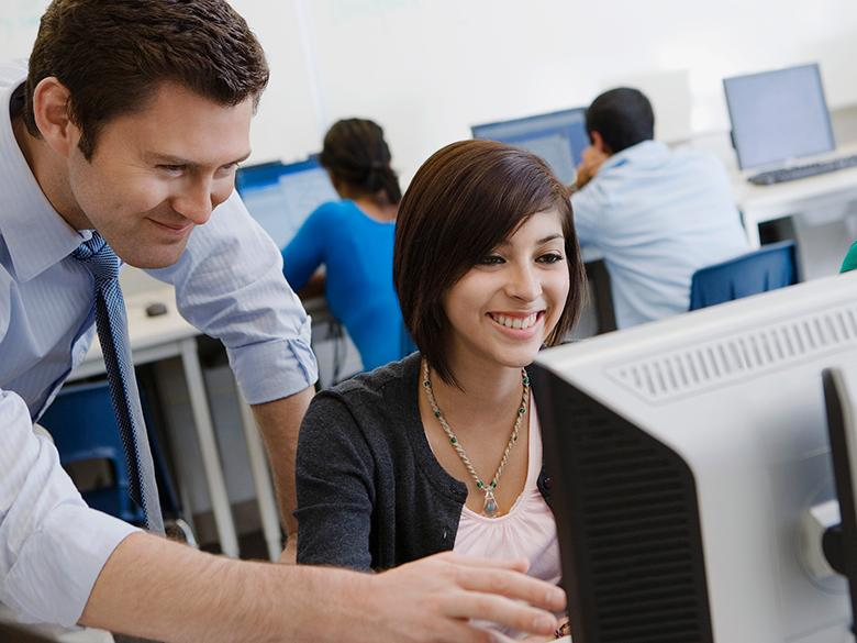A teacher helps a student sitting at a computer