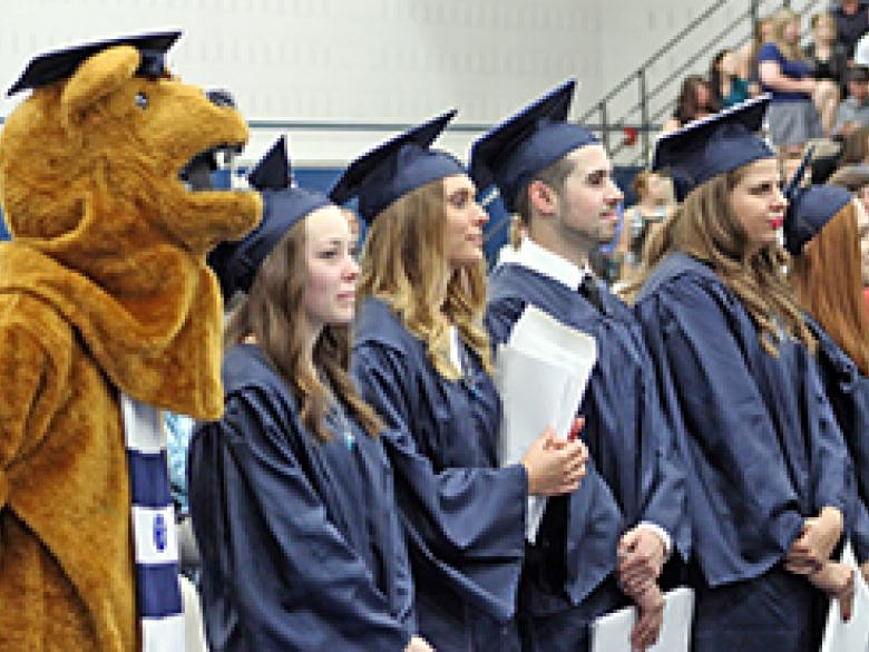 Students at Commencement stand at attention with Nittany Lion