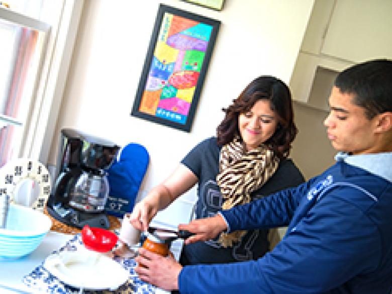 An Occupational Therapy student works with another student in a kitchen