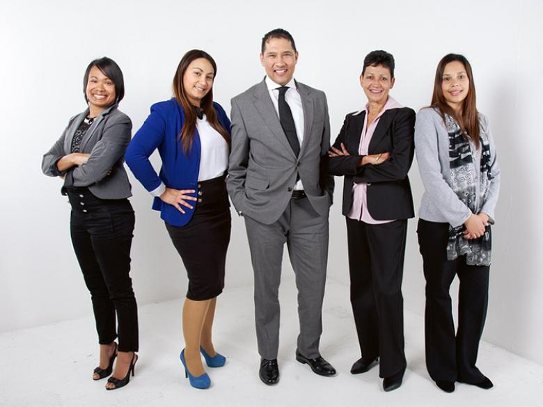 Five individuals in professional attire pose for group shot