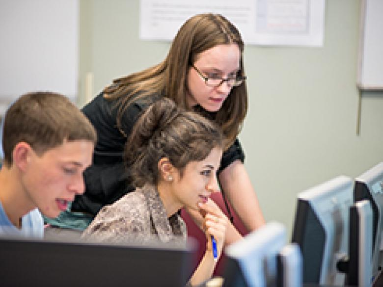 Penn State Mont Alto staff member helps a student at a computer workstation