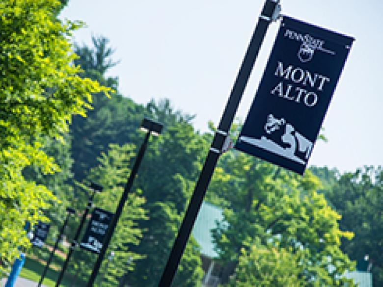Banner hangs over a sidewalk at Penn State Mont Alto