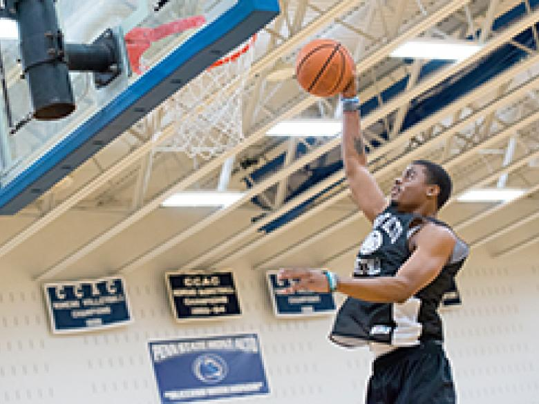 Student makes a jump shot in campus basketball court