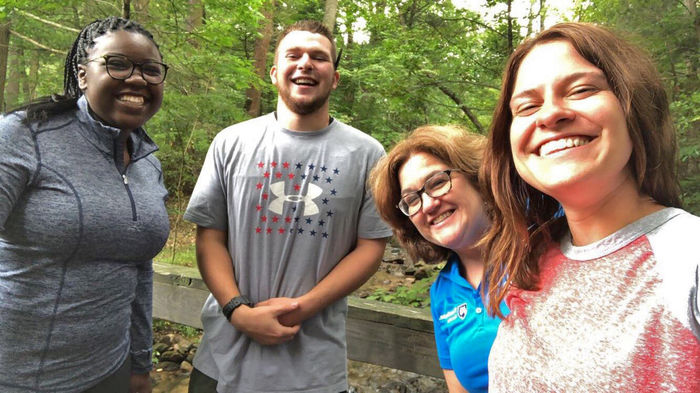 Several students take selfie with staff member in woods