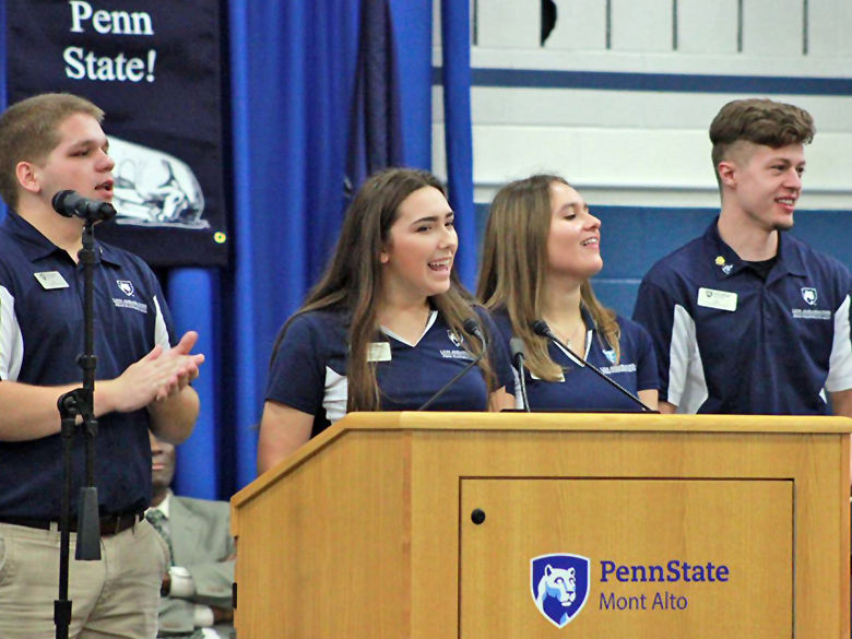 Penn State students stand at podium