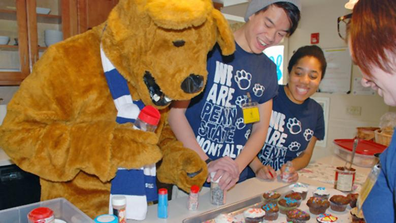 Lion Ambassadors bake muffins and cupcakes during a service project with the Nittany Lion's help