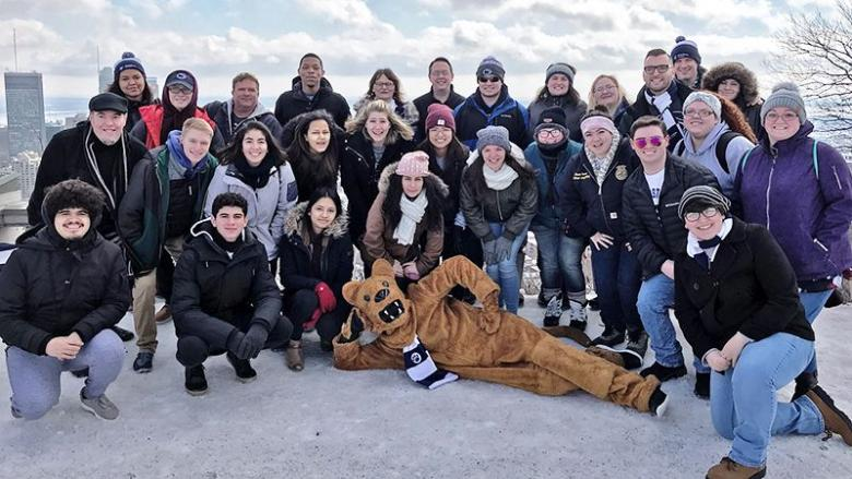 Group of Penn State students and chaperones pose in a lofty patio area overlooking Montreal