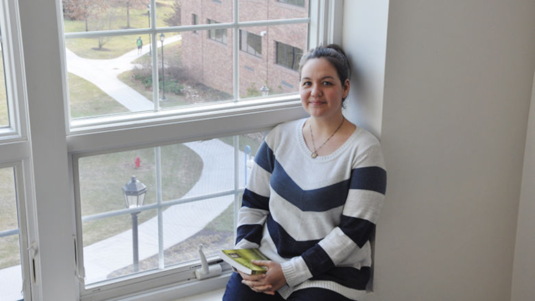 Female student sits in third story window overlooking quad