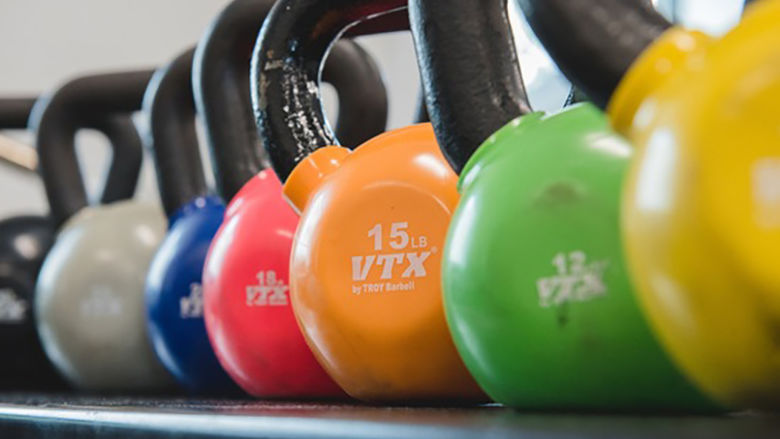 Kettlebells of many colors in a row